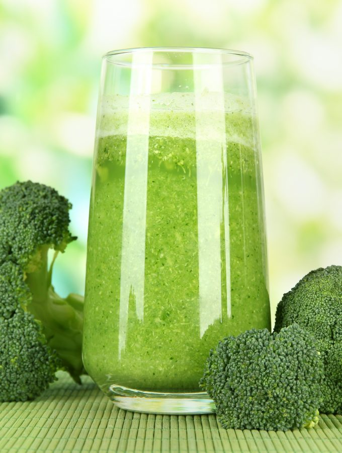 Glass of broccoli juice, on bamboo mat, on green background